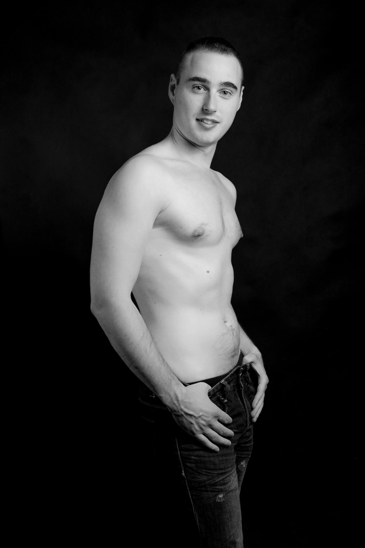 Profesionální ateliérové foto služby, černobílá fotografie mladý, svalnatý muž, mužský akt
